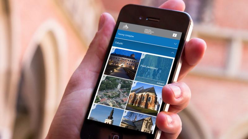 Smartfon z wyświetloną aplikacją Uniejów turystyczny
