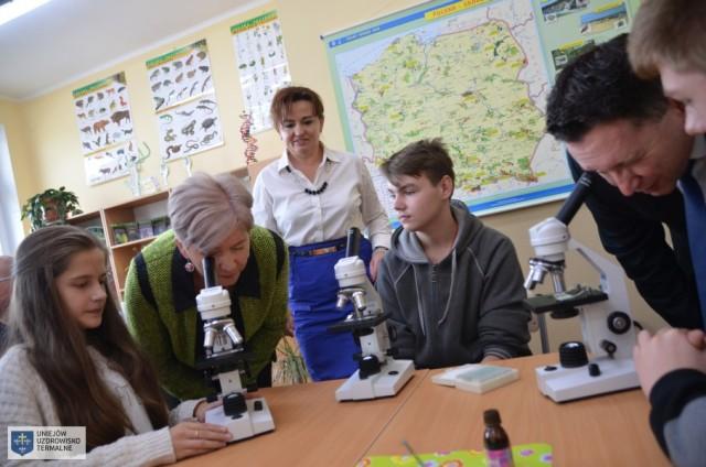 Osoby oglądaja coś przez mikroskopy